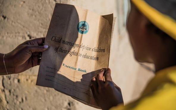 Flicka håller övningsbok om sina rättigheter SHR, barnäktenskap.
