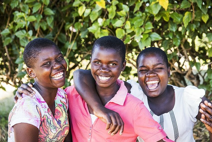 Three young Malawi girls smile and hug each other