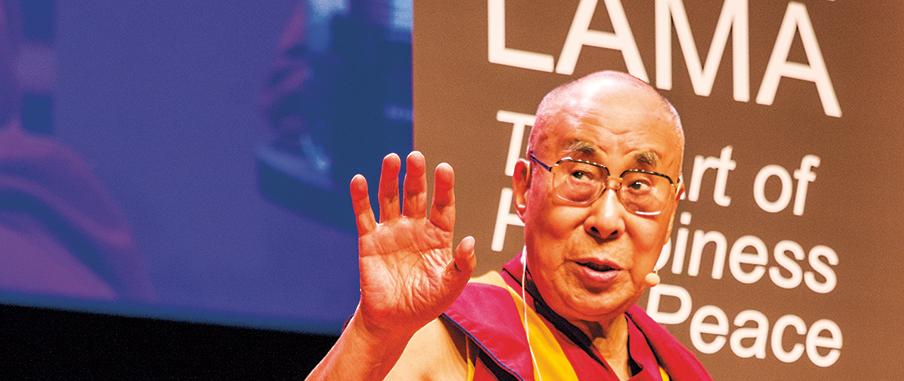 Dalai Lama står på scen i Malmö Live och vinkar mot publiken.