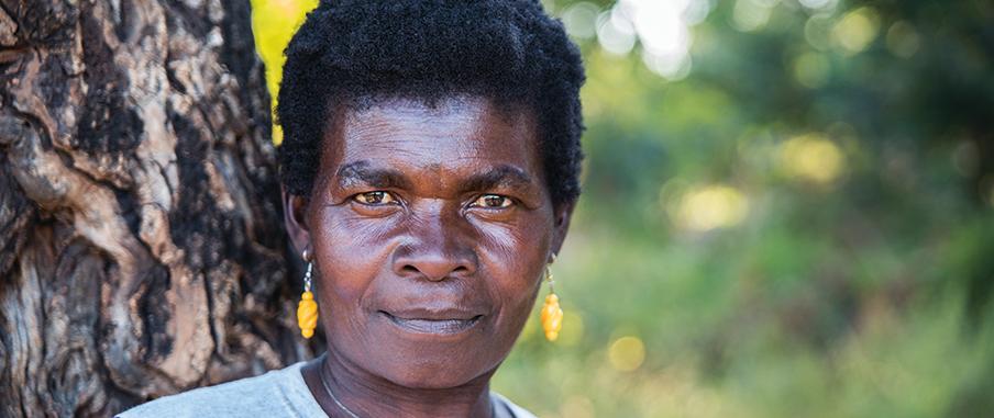 Martha Bikeyi står mot ett träd och tittar rätt in i kameran med en bestämd blick. Hon bär gula örhänge och ett silvrigt halsband.