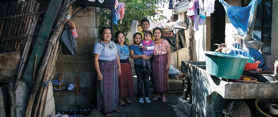 På bilden ser vi Andrea och hennes familj. De står på en innergård med tvättlinor omkring sig.