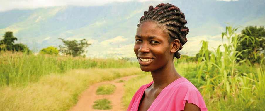 Alinafe står på en grusväg. Bakom henne finns ett bergigt landskap.