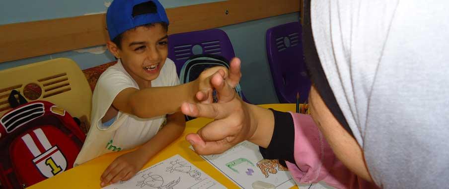 Ali håller sin speciallärare i handen. Framför dem finns några teckningar.