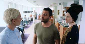 Servitris pratar med två restauranggäster som vill ha bord i restaurangen