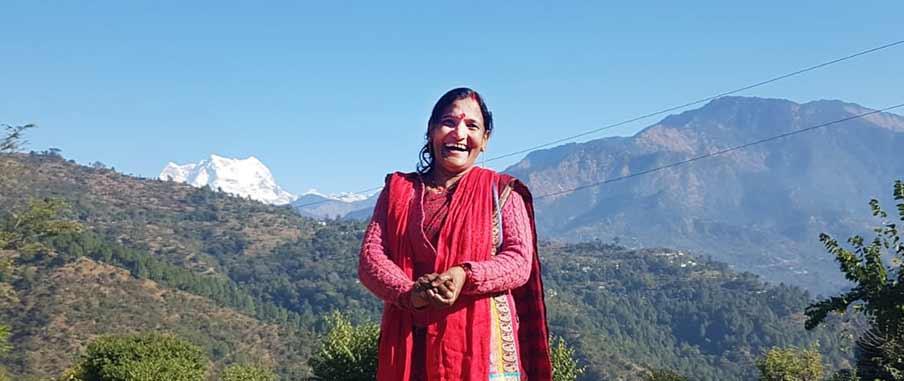 Sunita står på en kulle med snöklätt Himalaya i bagrunden.