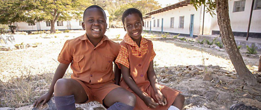 Två barn i orange skoluniformer sitter bredvid varandra under skuggan av ett träd. De ler in i kameran. I bakgrunden syns en solupplyst gård med vita byggnader.