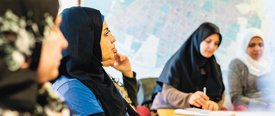 Fem kvinnor lyssnar uppmärksamt på någon utanför bilden. En av dem antecknar. På väggen bakom dem syns en karta.