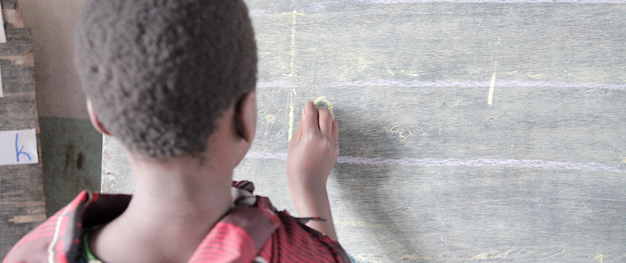 En flicka står och skriver på en griffeltavla