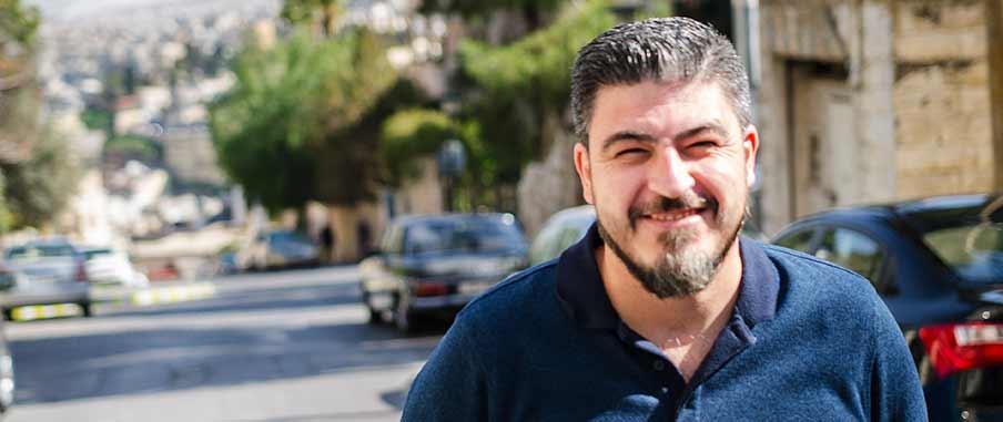 Suhaib ler in i kameran och kisar mot solljuset. I bakgrunden syns en gata med träd och bilar.