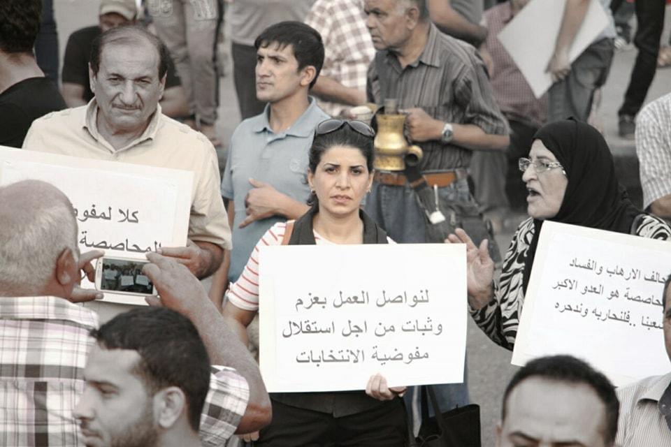 Intisar Al-Amyal med ett plakat i en protest.