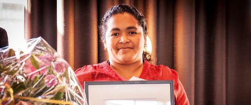På bilden ser vi María Teresa Rivera. Hon står med en blombukett och ett diplom i handen.